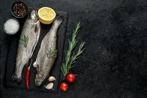 Surowy pstrąg rybny z przyprawami gotowy do gotowania na kamiennym tle