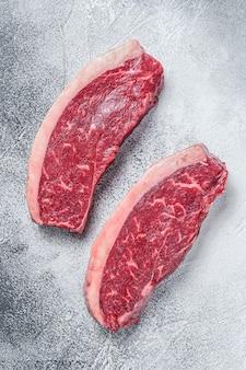 Surowy rumsztyk lub stek wołowy z polędwicy wołowej. białe tło. widok z góry.