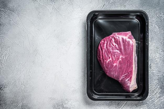 Surowy rumsztyk lub stek wołowy z polędwicy wołowej w opakowaniu próżniowym