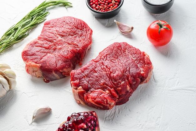 Surowy rumsztyk, mięso wołowe zagrodowe z przyprawami, rozmarynem, czosnkiem, granatem. białe tło z teksturą. widok z boku.