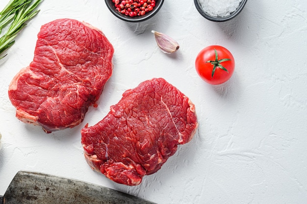 Surowy rumsztyk, mięso z wołowiny zagrodowej z przyprawami, rozmarynem, czosnkiem i tasakiem rzeźniczym. białe tło z teksturą. przestrzeń widokowa z góry za cenę.