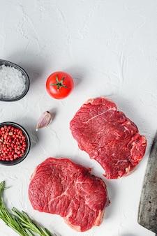 Surowy rumsztyk, mięso z wołowiny zagrodowej z przyprawami, rozmarynem, czosnkiem i tasakiem rzeźniczym. białe tło z teksturą. widok z góry w pionie.