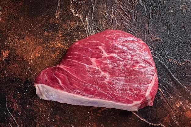 Surowy rumsztyk pokrojony lub stek z polędwicy wołowej na stole rzeźnika. ciemne tło. widok z góry.