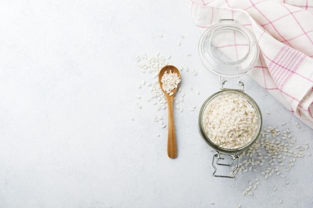 Surowy ryż biały arborio do dań z włoskiego risotto w szklanym słoju na białym betonie lub kamieniu.