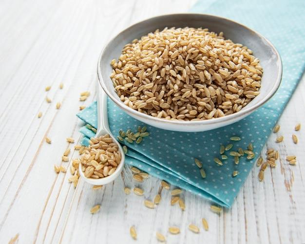 Surowy ryż brązowy na białym tle drewniane