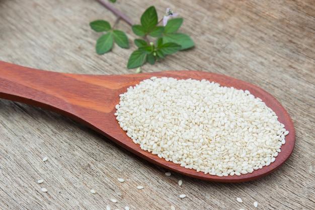 Surowy sezam na drewnianej łyżce dla zdrowego łasowania