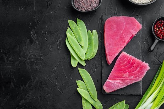 Surowy sezamowy zestaw składników stek z tuńczyka, na kamiennej desce, na czarnym kamiennym tle, płaski widok z góry, z copyspace i miejscem na tekst