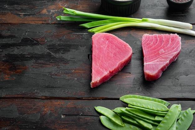 Surowy sezamowy zestaw składników stek z tuńczyka, na starym ciemnym tle drewnianego stołu, z copyspace i miejscem na tekst