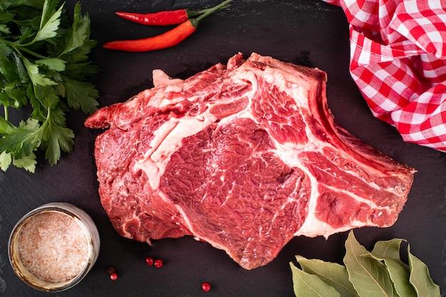 Surowy soczysty stek mięsny gotowy do grillowania na czarnej płycie łupkowej. stek z kością, cielęcina na drewnianej desce do krojenia z pomidorami koktajlowymi, ostrą papryką i ziołami. widok z góry