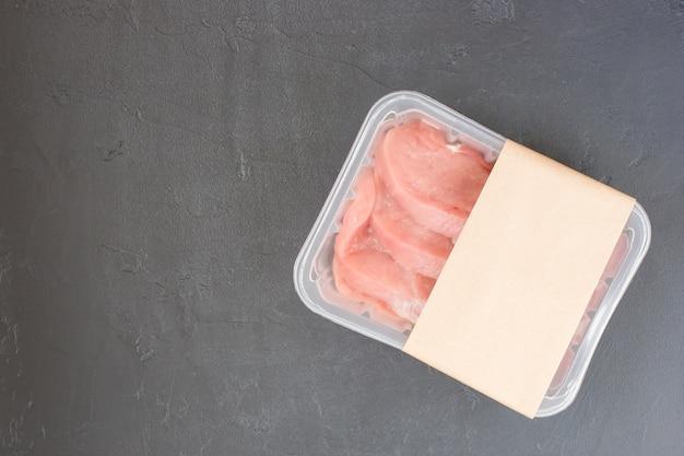 Surowy stek, antrykot w plastikowym opakowaniu próżniowym na czarnym tle. projekt układu logo.