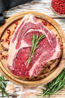 Surowy stek kowbojski lub ribeye na kości na desce do krojenia