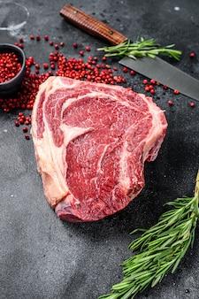 Surowy stek kowbojski lub ribeye na kości z ziołami. marmurowa wołowina. czarne tło. widok z góry.