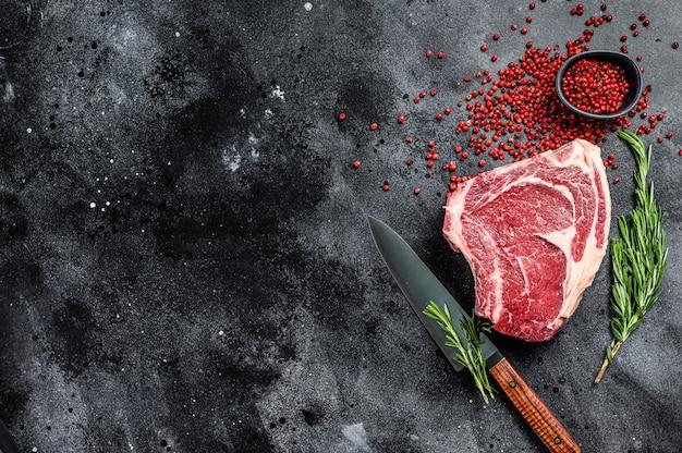 Surowy stek kowbojski lub ribeye na kości z ziołami