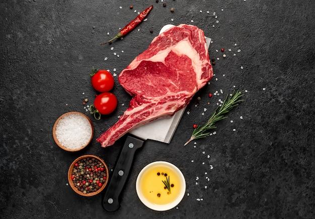 Surowy stek kowbojski z przyprawami na nóż na kamiennym tle
