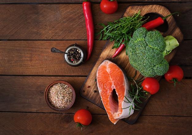 Surowy stek łosoś i warzywa do gotowania na drewnianym stole w stylu rustykalnym. widok z góry