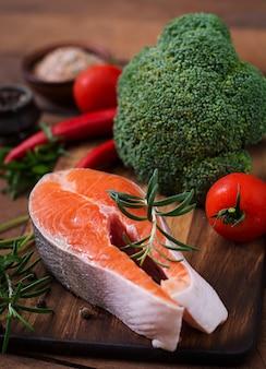 Surowy stek łosoś i warzywa do gotowania na drewnianym stole w stylu rustykalnym.