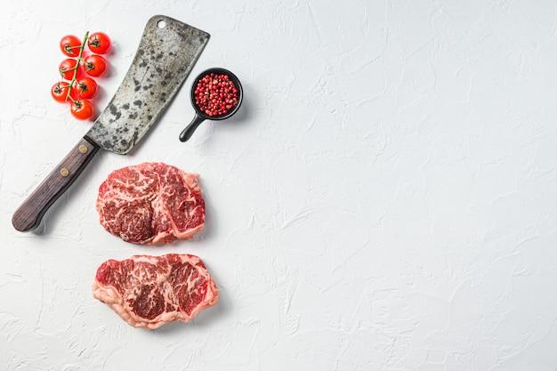 Surowy stek, mięso ekologiczne z przyprawami i tasakiem rzeźniczym. białe tło z teksturą. widok z góry z miejscem na tekst.