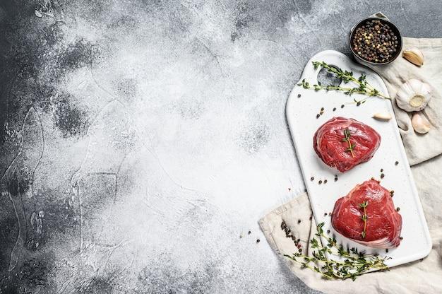 Surowy stek mignon filet na białej desce do krojenia. polędwica wołowa. szare tło. widok z góry. miejsce na tekst