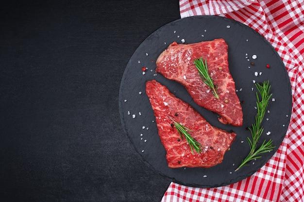 Surowy stek na desce do krojenia z rozmarynem i przyprawami
