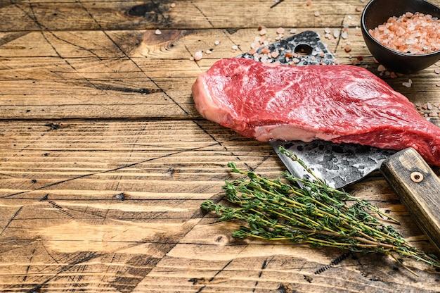 Surowy stek nowojorski na tasaku, mięso wołowe.