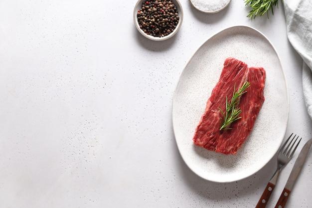 Surowy stek ribeye z rozmarynem na białym tle. skopiuj miejsce