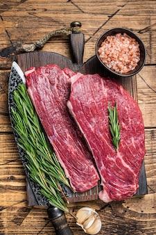 Surowy stek rumszkowy lub stek picanha na drewnianej desce z nożem rzeźniczym