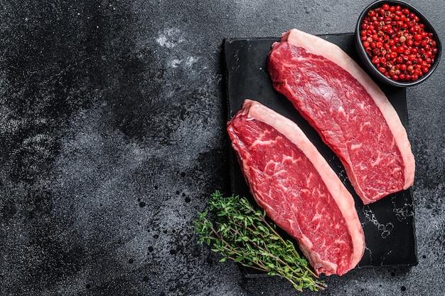 Surowy stek rumsztyk lub stek z polędwicy wołowej na marmurowej desce na drewnianym stole. widok z góry.