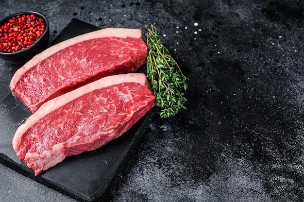 Surowy stek rumsztyk lub stek z polędwicy wołowej na marmurowej desce.