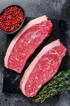 Surowy stek rumsztyk lub stek z polędwicy wołowej na marmurowej desce