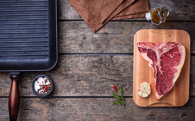 Surowy stek t-bone i żelazna patelnia do grilla