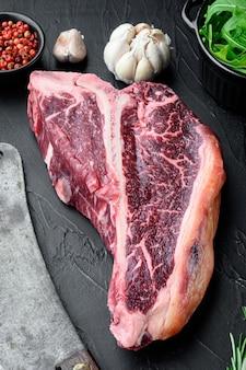 Surowy stek t-bone na grilla lub bbq z zestawem składników, na czarnym kamiennym tle