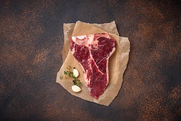 Surowy stek t-bone z czosnkiem i tymiankiem