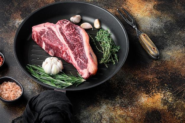 Surowy stek t-bone z surowego świeżego mięsa z zestawem przypraw, czosnku i rozmarynu, na patelni żeliwnej, na starym ciemnym tle rustykalnym