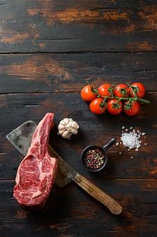 Surowy stek tomahawk na tasaku do mięsa. ekologiczna marmurkowa wołowina rasy czarnej angus. ciemne drewniane tło. widok z góry. z przyprawami, pieprzem, rozmarynem, solą, czosnkiem. miejsce na tekst nikt