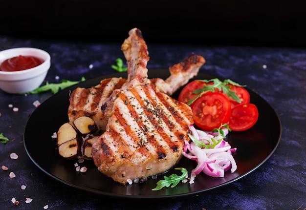 Surowy stek wieprzowy z ziołami na ciemnej powierzchni. surowy soczysty stek z kością