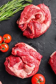 Surowy stek wołowy chuck roll, z ziołami, przyprawami na czarnym stole, widok z góry.