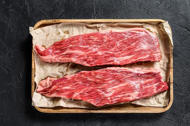 Surowy stek wołowy, flanka. marmurowa wołowina czarne tło. widok z góry