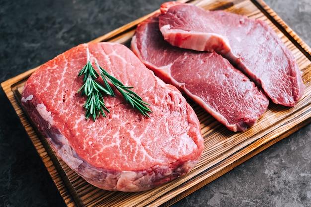Surowy stek wołowy i antrykot na drewnianej desce z bliska