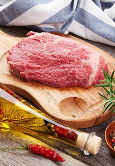 Surowy stek wołowy i przyprawy na drewnianym stole