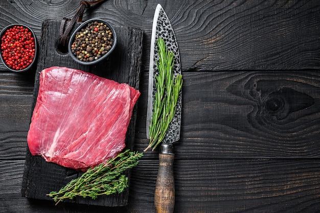 Surowy stek wołowy lub wołowy bavette na drewnianej desce do krojenia. czarne tło. widok z góry. skopiuj miejsce.