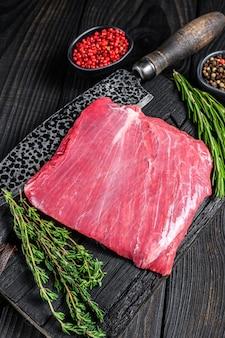 Surowy stek wołowy lub wołowy bavette na drewnianej desce do krojenia. czarne tło. widok z góry.