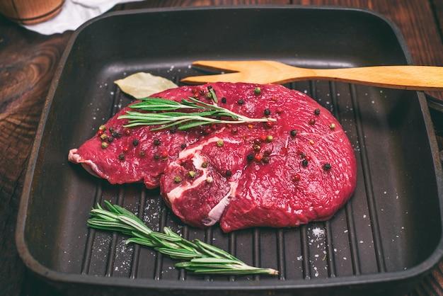 Surowy stek wołowy na czarnej patelni quart