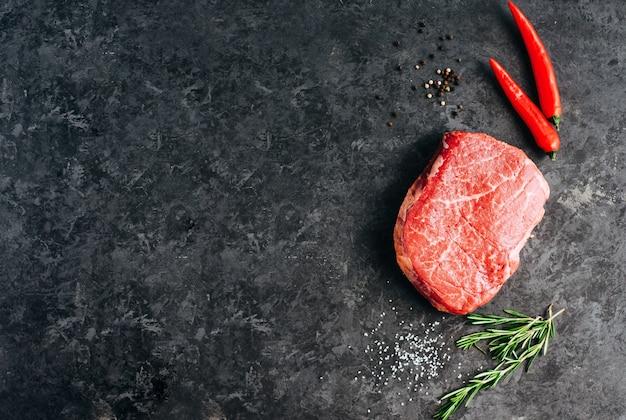 Surowy stek wołowy na czarnym tle z rozmarynem papryczką chili i przyprawami kopia miejsce