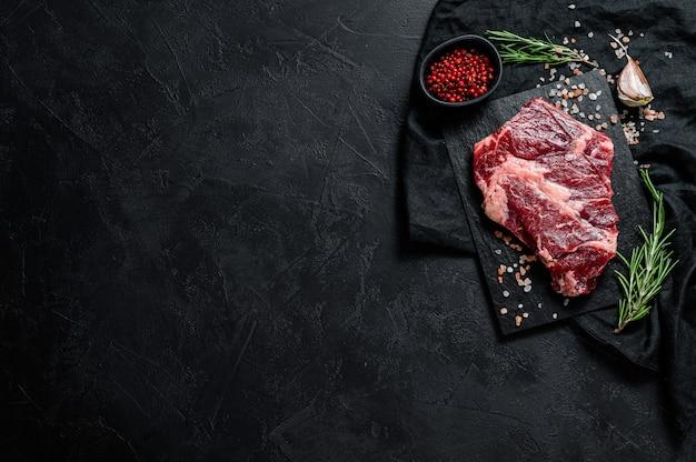 Surowy stek wołowy na desce do krojenia. tło ekologiczne mięso rolnicze