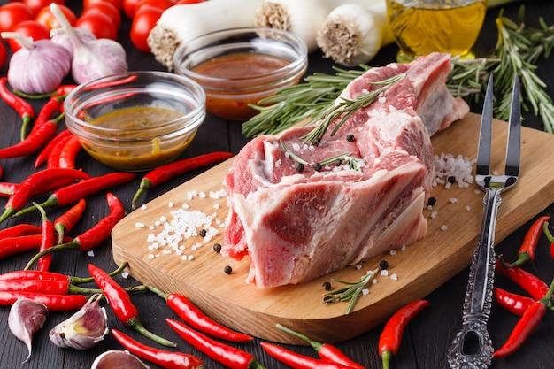Surowy stek wołowy na desce do krojenia z ziołami i warzywami