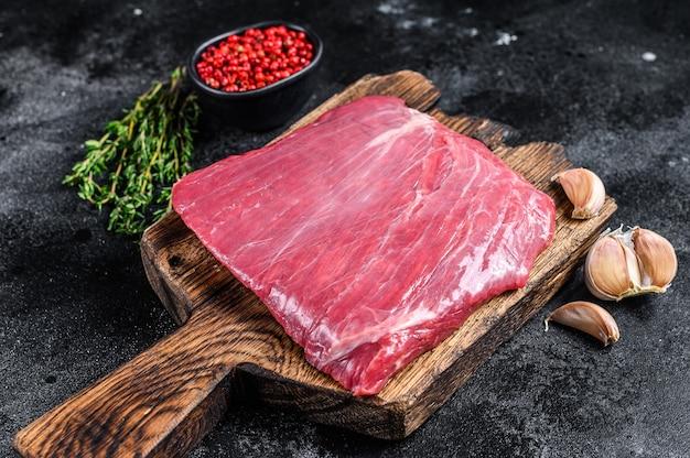 Surowy stek wołowy na desce do krojenia