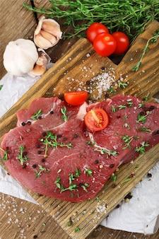 Surowy stek wołowy na drewnianym stole