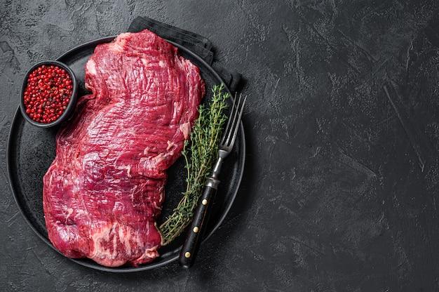 Surowy stek wołowy obtocz lub połóż na talerzu z tymiankiem. czarne tło. widok z góry. skopiuj miejsce.