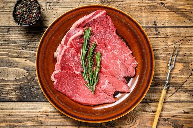 Surowy stek wołowy posiekać na talerzu.