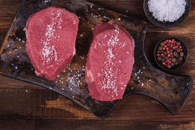 Surowy stek wołowy posypany solą. widok powyżej mięsa